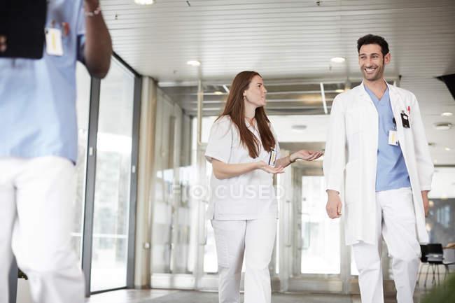 Jóvenes trabajadores de la salud sonrientes discutiendo mientras caminan en el vestíbulo en el hospital - foto de stock