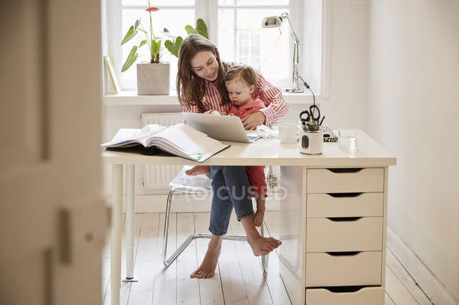 Female accountant sitting with daughter while working on laptop at home — Stock Photo