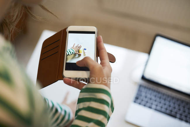 Imagen recortada del blogger fotografiando productos de belleza en casa - foto de stock