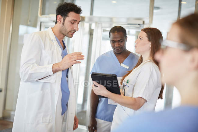Confident multi-ethnic nurses and doctors discussing over digital tablet in lobby at hospital — Stock Photo