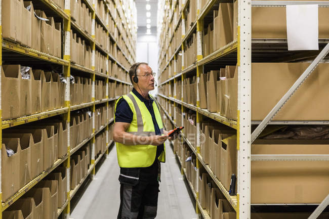 Vue latérale du travailleur masculin senior avec tablette numérique regardant les paquets sur rack tout en parlant à travers casque à la distribution — Photo de stock
