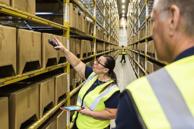 Trabajadora mujer sosteniendo tableta digital mientras apunta a caja de cartón en rack a compañero de trabajo en el almacén de distribución - foto de stock