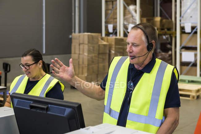 Confident senior senior representante de servicio al cliente masculino hablando a través de auriculares mientras está de pie junto a una compañera de trabajo en distr - foto de stock