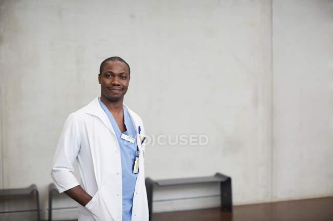 Retrato do doutor masculino confiável que está com mãos nos bolsos de encontro à parede no hospital — Fotografia de Stock
