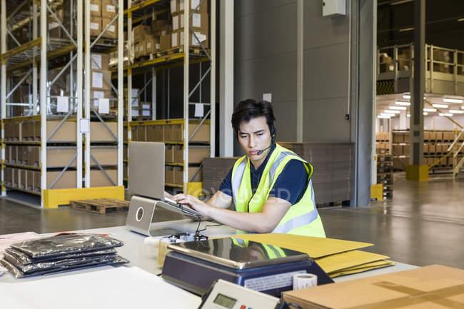 Confiado joven representante de servicio al cliente masculino usando computadora portátil mientras está sentado en el escritorio en el almacén - foto de stock