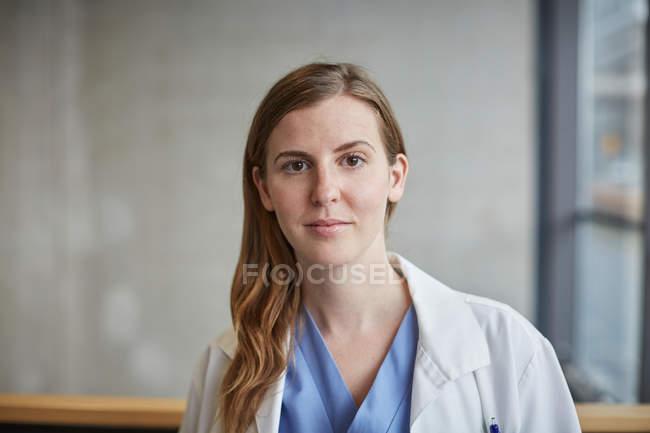 Retrato do doutor fêmea adulto meados de confiável que está no corredor no hospital — Fotografia de Stock