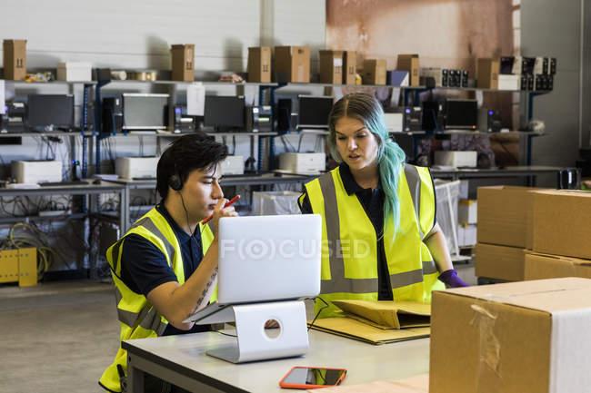 Representante de servicio al cliente joven y confiado discutiendo con el compañero de trabajo sobre la computadora portátil mientras está en el escritorio en el almacén - foto de stock