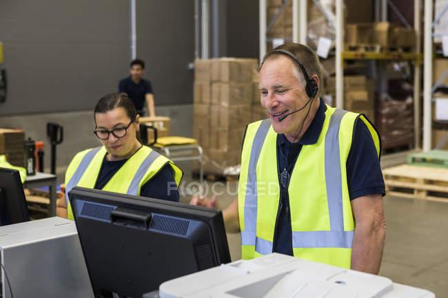 Seguro alto representante de servicio al cliente masculino hablando a través de auriculares mientras está de pie a su compañero de trabajo en la distribución - foto de stock