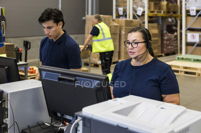 Confident y madura representante de servicio al cliente hablando a través de auriculares mientras está de pie junto a un compañero de trabajo en distributi - foto de stock