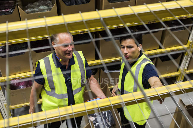 High angle view of male coworkers discussing while seen through rack shelf at warehouse — стокове фото