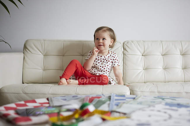 Thoughtful girl sitting on sofa at home — Stock Photo