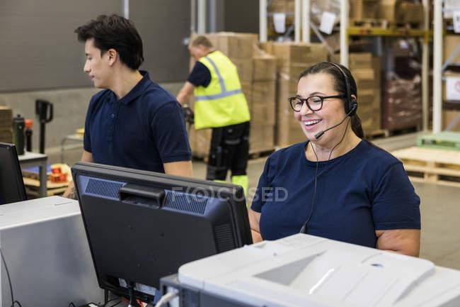 Representante de servicio al cliente femenino sonriente hablando a través de auriculares mientras está de pie junto a un compañero de trabajo en la distribución - foto de stock
