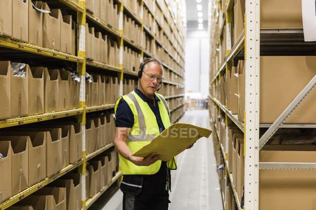 Travailleur masculin senior regardant paquet tout en parlant à travers casque debout au milieu des rayonnages à l'entrepôt de distribution — Photo de stock