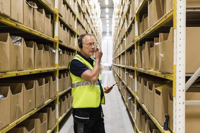 Travailleur masculin senior avec tablette numérique regardant les paquets sur rack tout en parlant à travers casque à l'entrepôt de distribution — Photo de stock