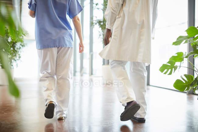 Sección baja de enfermera que camina con un médico masculino en el pasillo del hospital - foto de stock