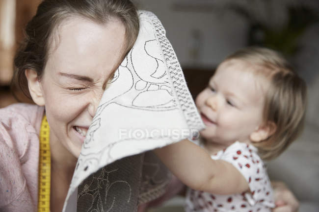 Cheerful fashion designer and daughter playing with cloth at home — Stock Photo