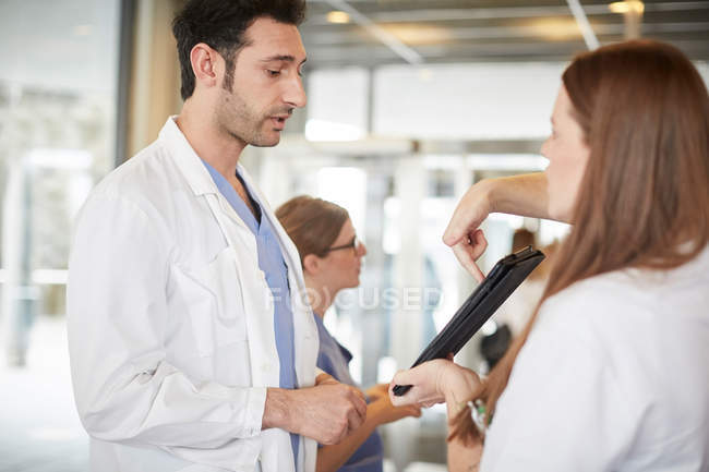 Young healthcare workers discussing over digital tablet while standing in lobby at hospital — Stock Photo