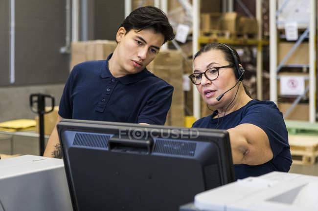 Confident y madura representante de servicio al cliente discutiendo con el compañero de trabajo sobre el monitor de la computadora en la distribución con - foto de stock