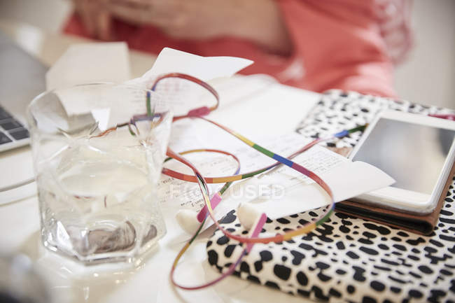 Close up of multi colored earphones and financial bills with smart phone on table — Stock Photo
