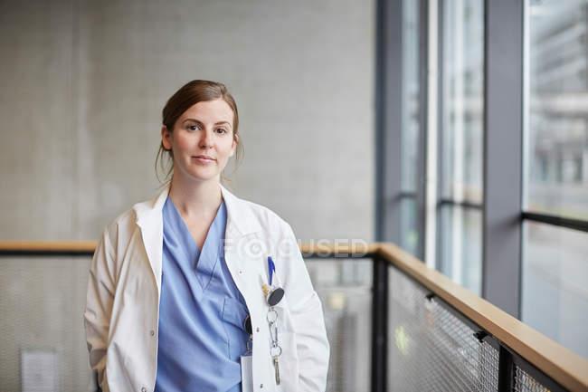 Retrato de médico feminino adulto médio confiante pela janela no corredor no hospital — Fotografia de Stock