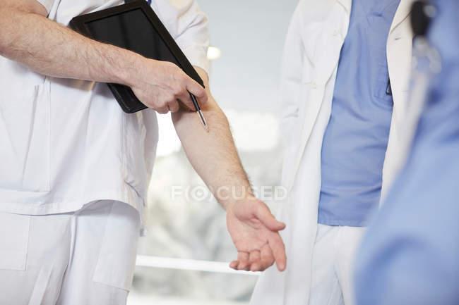 Sección media de la enfermera masculina gesturing mientras está de pie con compañeros de trabajo en el hospital - foto de stock