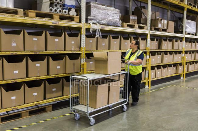 Chariot de poussée femelle sur toute la longueur avec boîtes en carton par rack à l'entrepôt — Photo de stock