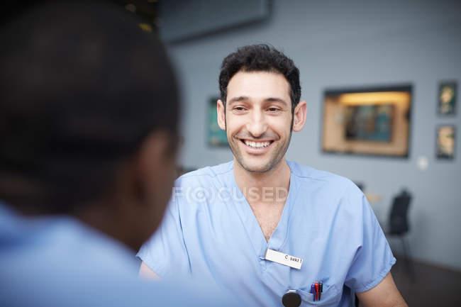 Enfermera varón sonriente hablando con un compañero de trabajo en la cafetería en el hospital - foto de stock