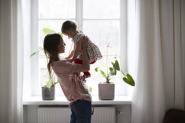 Side view of fashion designer carrying daughter while standing by window at home — Stock Photo