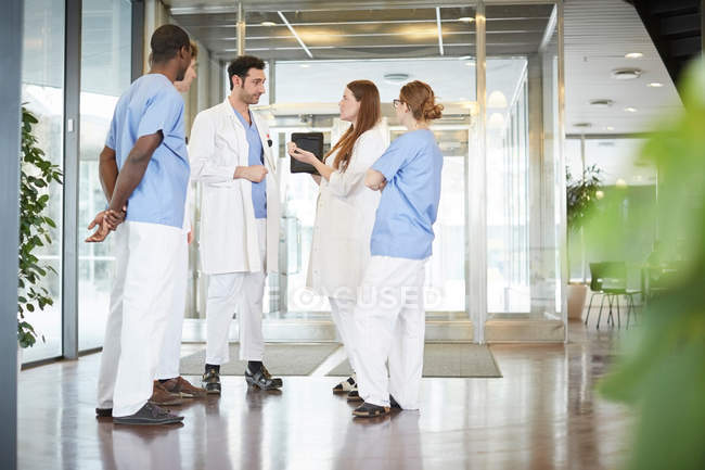 Full length of multi-ethnic healthcare team discussing while standing at lobby in hospital — Stock Photo