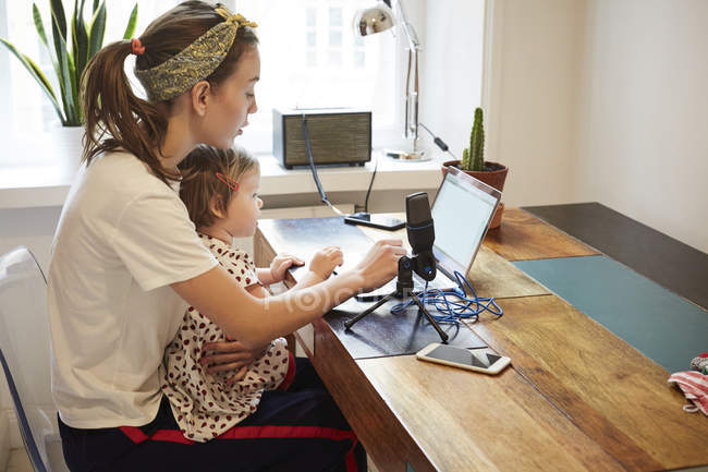 Podcaster sitting with daughter while marketing through laptop at home — Stock Photo