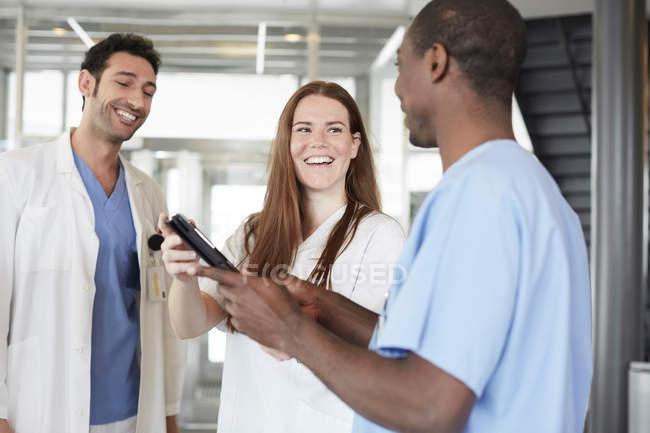 Los trabajadores de la salud multiétnicos sonrientes discutiendo sobre la tableta digital mientras están en el vestíbulo en el hospital - foto de stock