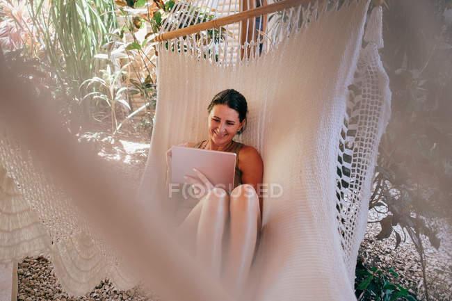 Mujer madura sonriente usando tableta digital en hamaca en la playa - foto de stock