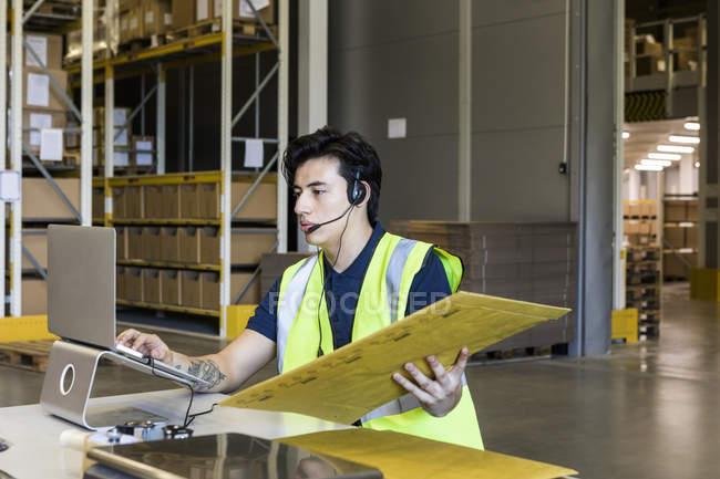 Уверенный молодой мужчина представитель обслуживания клиентов с помощью ноутбука, сидя с пакетом на столе на складе — стоковое фото