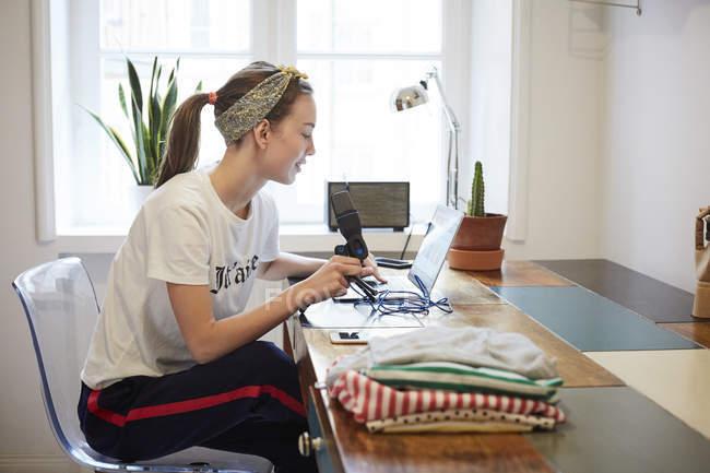 Podcaster usando laptop sentado en la silla en casa - foto de stock