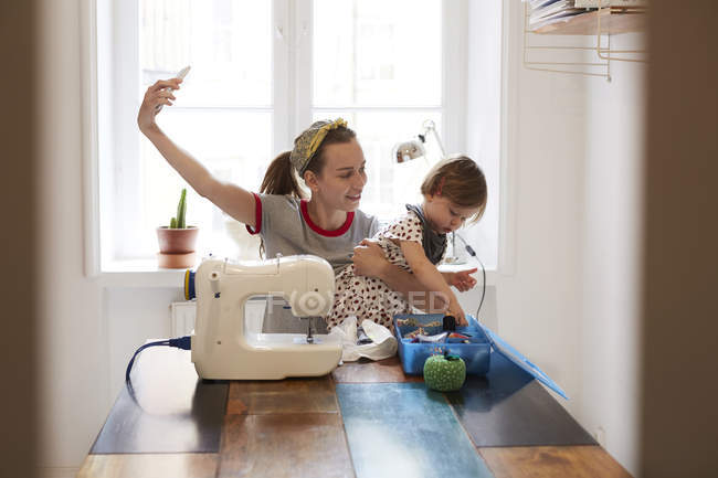 Female tailor taking selfie with daughter through smart phone while sitting on table at home — Stock Photo