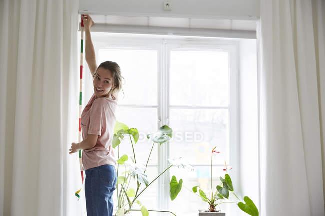 Lächelnder Designer misst Fenster zu Hause mit Maßband — Stockfoto