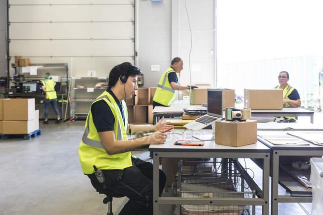 Joven representante de servicio al cliente hablando a través de auriculares mientras compañeros de trabajo en el almacén - foto de stock