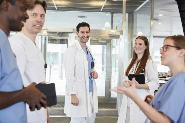 Smiling multi-ethnic healthcare team discussing at lobby in hospital — Stock Photo