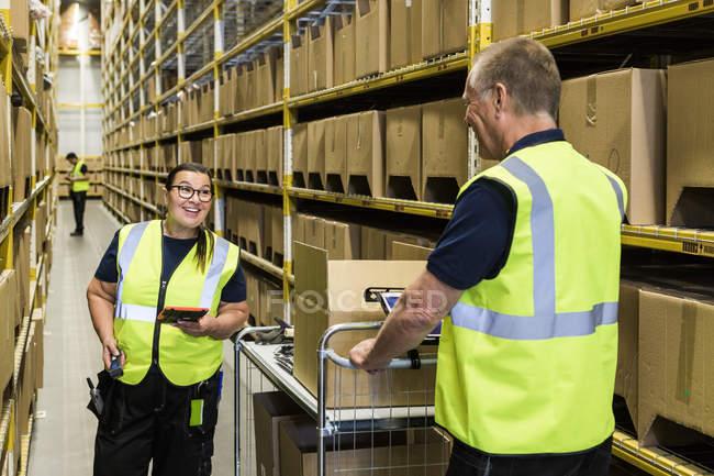 Travailleurs souriants discutant tout en se tenant debout sur l'allée au milieu des rayonnages à l'entrepôt de distribution — Photo de stock