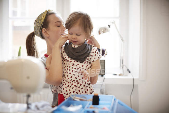Female tailor tying scarf on daughter's neck while sitting at home — Stock Photo