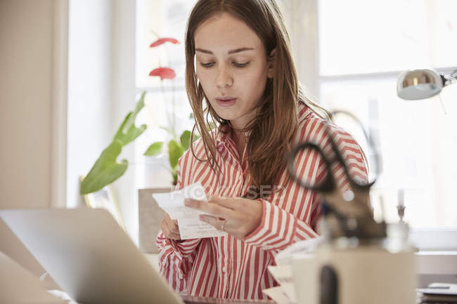 Young woman examining financial bill while using laptop at home — Stock Photo