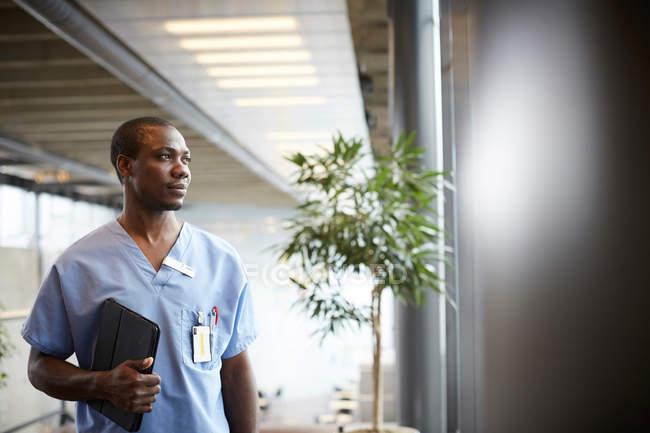 Enfermeira adulta média cuidadosa com tablet digital olhando pela janela enquanto estava no corredor no hospital — Fotografia de Stock