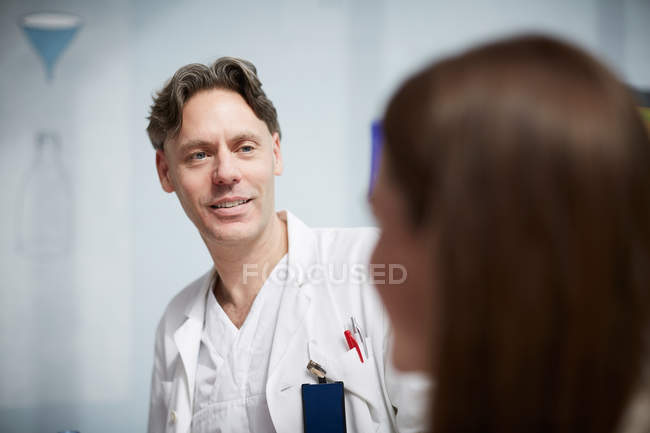 Médico maduro sonriente mirando a una compañera de trabajo mientras está sentada en la cafetería del hospital - foto de stock