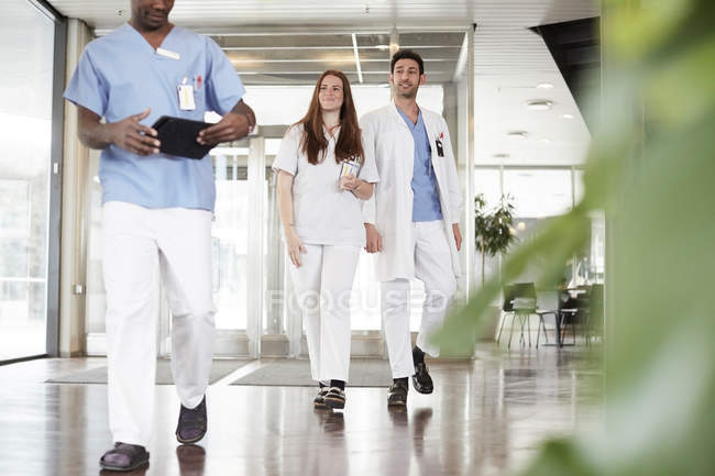Confident healthcare workers walking in lobby at hospital — Stock Photo