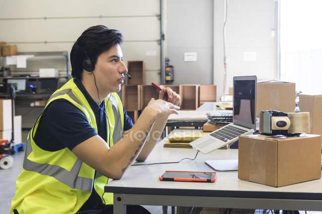 Вид сбоку уверенного молодого мужчины представитель обслуживания клиентов говорить через гарнитуру, сидя за столом на складе — стоковое фото
