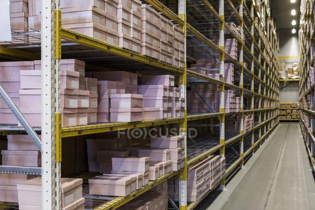Пакети на стелажах вузького порожнього проходу на розподільчому складі — стокове фото
