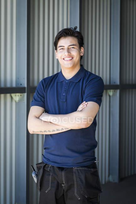 Retrato de sorridente jovem trabalhador do sexo masculino de pé com os braços cruzados na entrada do armazém — Fotografia de Stock