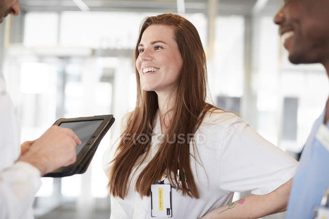 Smiling multi-ethnic healthcare workers discussing over digital tablet in lobby at hospital — Stock Photo