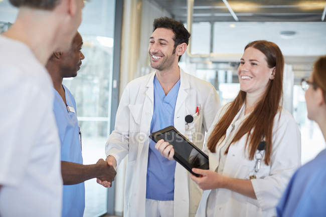 Equipe multi-ethnic de sorriso dos cuidados médicos que está na entrada no hospital — Fotografia de Stock