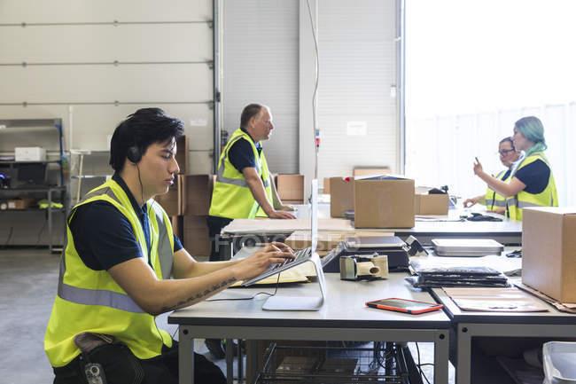 Confiado joven representante de servicio al cliente masculino usando computadora portátil mientras compañeros de trabajo discuten en el escritorio en el almacén - foto de stock